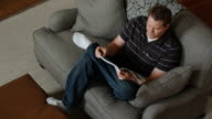 father reading a magazine on the couch