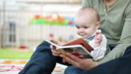 CU Father reading book to daughter  (0-11 months) / Brussels, Belgium