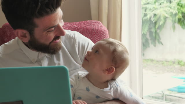 Father reads son a bedtimes story on the laptop.