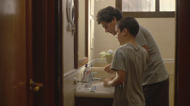 MS Father shaving and son (10-11) brushing in bathroom / Havana, Cuba