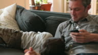 MS Father showing cell phone to son (4-5) on couch / Brooklyn, New York City, USA