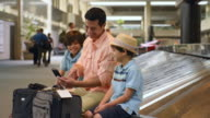 Father showing sons how to use cell phone at airport