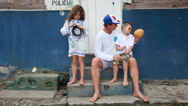 Father shows coconut to son and then surprises daughter.