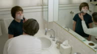 Father smearing shaving foam on face of his son and his own