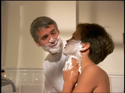 Father + son looking in bathroom mirrior shaving together + play-fighting with shaving cream