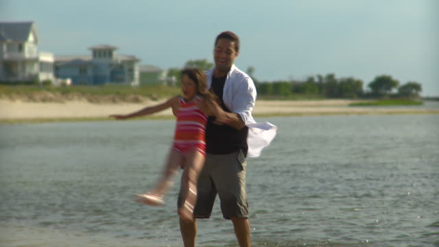 MS Father spinning daughter (8-9) around in the air on beach, Eastville, Virginia, USA