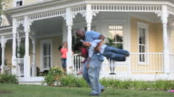 WS Father swinging two children around in front yard of home / Richmond, Virginia