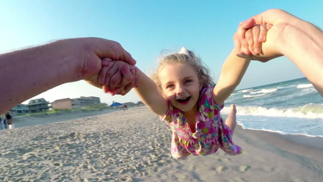 Father swings daughter around as waves break on sunny beach