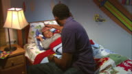 MS, father taking son's (6-7) temperature in bed, Westfield, New Jersey, USA