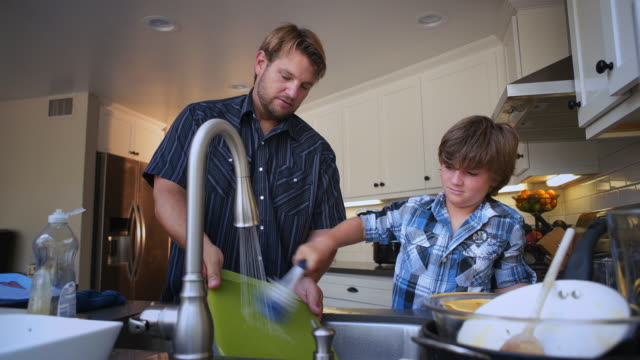 Father teaches son to clean the dishes with some good old fashoined elbow grease.