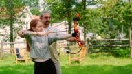 Vater lehrt seine Teenager-Tochter, einen Bogen zu schießen