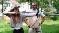 Father teaching his teenager daughter to shoot a bow