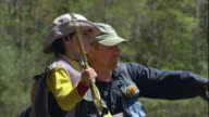 CU Father teaching son (8-9) fly fishing, standing in river / Maine, USA