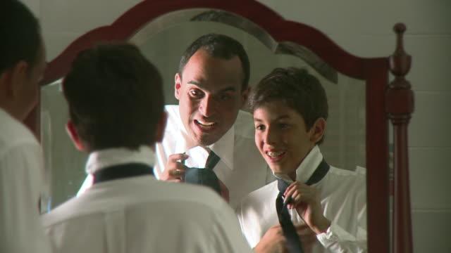 CU Father teaching son (12-13) tying tie, Panama City, Panama