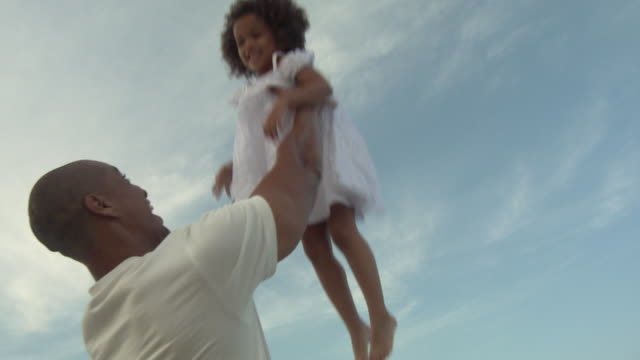 MS SLO MO Father throwing daughter (4-5) on beach / Jacksonville, Florida, USA