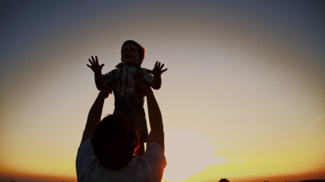 SLO MO Father throwing his son up in the air