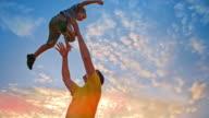 SLO MO vader zijn zoon gooien in de lucht bij zonsondergang