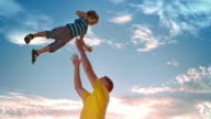 SLO MO Father tossing his son into the air in sunshine