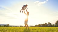 SLO MO DS Father tossing his son into the air outside in sunshine