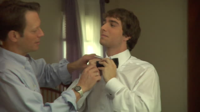 CU, Father tying teenage boy's (16-17) bowtie in front of mirror, Edison, New Jersey, USA