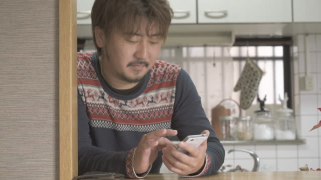 Father using a smart phone in the kitchen counter