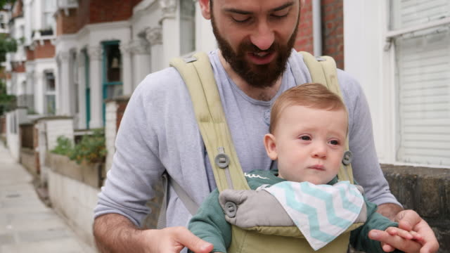CU of father walking down city road with son in baby carrier.