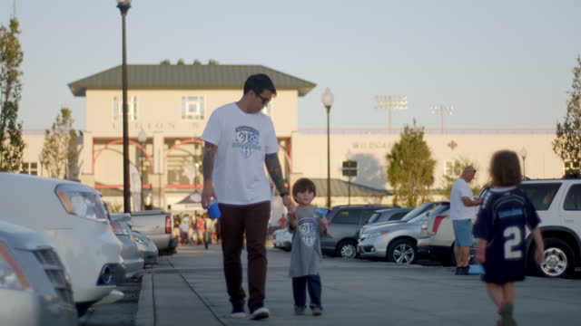 WS SLO MO. Father walks holding young son's hand outside crowded sports stadium.