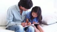 Father watching his daughter colouring