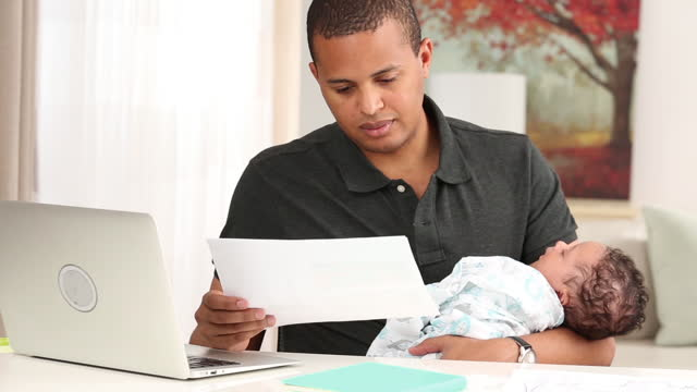 Father with newborn working at home on laptop