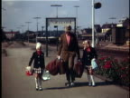 1970 WS Father with two girls (6-7, 8-9) wearing matching outfits on train station, Naestved, Denmark