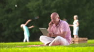 HD DOLLY: Father Working While Having Picnic With Family