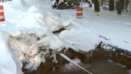 February 11 2010 PAN Huge hole in snow covered ground with orange construction cone and fire hydrant frozen into puddle and great mounds of snow to...