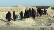 February 2009 WS PAN Group of women wearing burkha walking in desert / Bakwa Farah Province Afghanistan