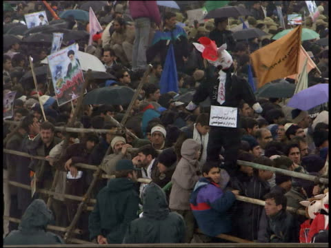 February 28 2001 MONTAGE Crowd waving signs and burning Uncle Sam effigies at first day of Ashura / Iran