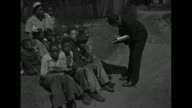 A federal census leans to interview an African American family and write in a ledger book / worker writes in book while talking to woman and children...