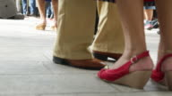 Feet and legs of a group of people dancing outdoors.