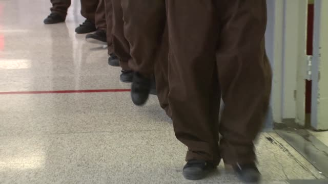 Feet and legs of teen inmates as they walk the halls of Rikers Island