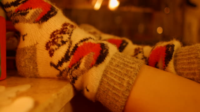 Feet girl with warm socks by the fireplace