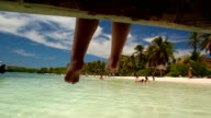 Feet hanging off pier on a beautiful desert island