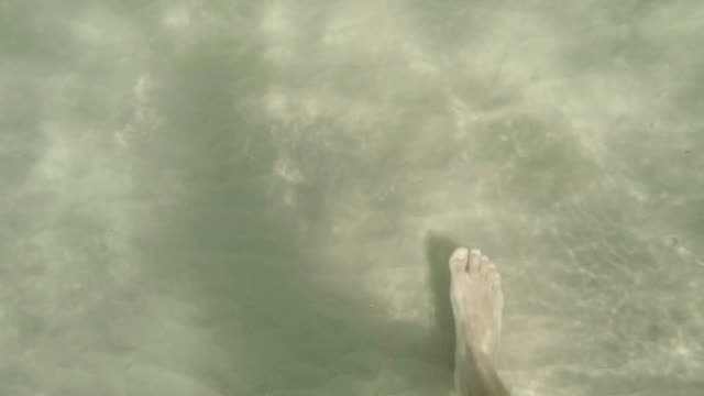 Feet in the water. Slow motion