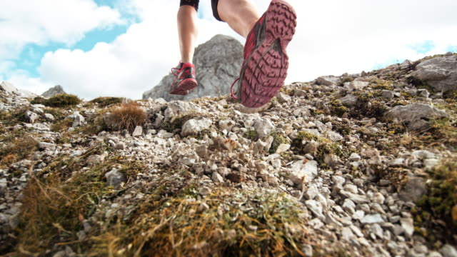 SLO MO Feet of a female runner scattering gravel on a high mountain trail