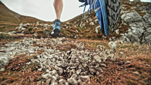 SLO MO LD Feet of a male runner causing gravel to scatter