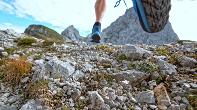 SLO MO Feet of a male runner scattering gravel on a high mountain trail