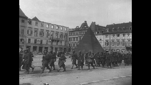 Feet of American soldier walking past dead German soldiers / VS Americans walk past ruined buildings men walking past 'pyramid' / sentry stands far...