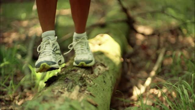 Feet of runner walking across moss-covered log in woods