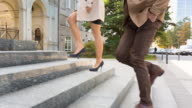 CU feet of well dressed couple hurrying up stairs