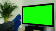 Feet up, watching chroma key TV and changing channel.