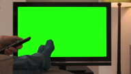 Feet up, watching chromakey TV and changing channel.