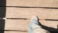 Feet walking in a bridge over a red river at Evans Head, New South Wales, Australia