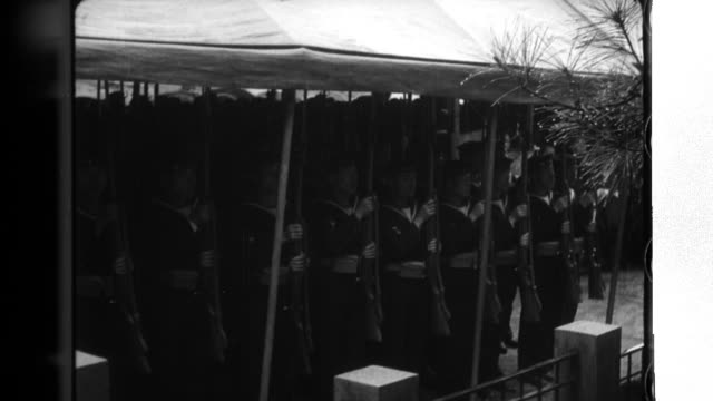 Fellow soldiers hold the remains of the dead as they solemnly march in Kure City Japan school children and citizens stand in a line to receive them...